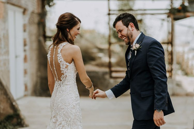 First Look Photo | Bride in Sleeveless High-Neck Stella York Gown with Lace Overlay and Gold Underskirt | Half Up Half Down Wedding Hair | Groom in Navy Suit and Floral Tie | Rifle Paper Co. Trainers for Informal Wedding in Fort Worth, Texas | Paul & Nanda Photography