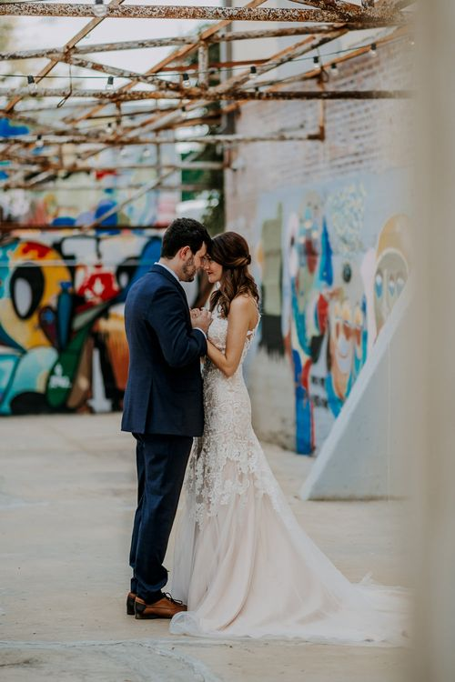 First Look Photo | Bride in Sleeveless High-Neck Stella York Gown with Lace Overlay and Gold Underskirt | Half Up Half Down Wedding Hair | Bride Wearing Red Lipstick | Groom in Navy Suit and Floral Tie | Rifle Paper Co. Trainers for Informal Wedding in Fort Worth, Texas | Paul & Nanda Photography