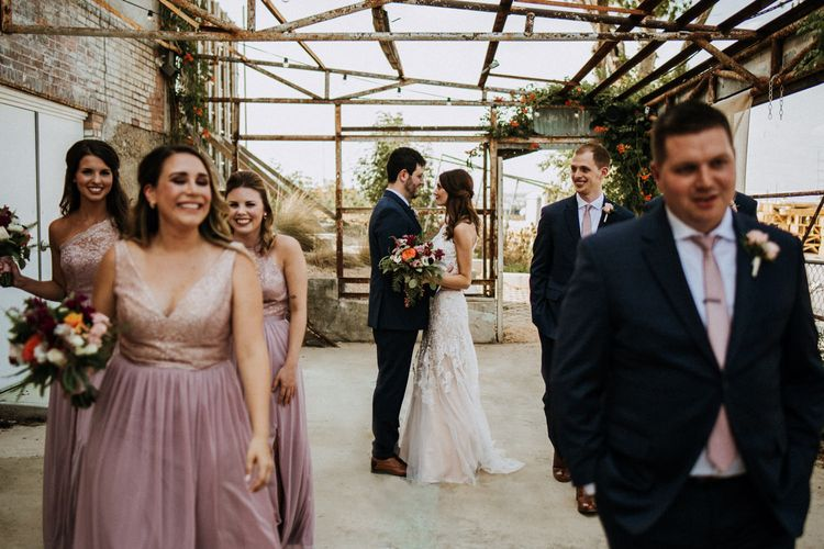 First Look Photo | Bride in Sleeveless High-Neck Stella York Gown with Lace Overlay and Gold Underskirt | Half Up Half Down Wedding Hair | Groom in Navy Suit and Floral Tie | Colourful Bridal Bouquet of Pink, Orange and White Flowers with Ferns, Eucalyptus and Greenery | Bridesmaids in Pink Dresses with Lace Bodice | Groomsmen in Navy Suits and Silk Blush Ties | Rifle Paper Co. Trainers for Informal Wedding in Fort Worth, Texas | Paul & Nanda Photography