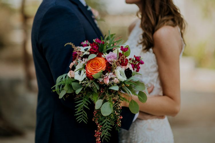First Look Photo | Bride in Sleeveless High-Neck Stella York Gown with Lace Overlay and Gold Underskirt | Half Up Half Down Wedding Hair | Groom in Navy Suit and Floral Tie | Colourful Bridal Bouquet of Pink, Orange and White Flowers with Ferns, Eucalyptus and Greenery | Rifle Paper Co. Trainers for Informal Wedding in Fort Worth, Texas | Paul & Nanda Photography