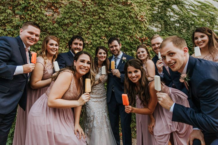 Bridal Party Eating Popsicles | Bride in Sleeveless High-Neck Stella York Gown with Lace Overlay and Gold Underskirt | Groom in Navy Suit and Floral Tie | Bridesmaids in Pink Dresses with Lace Bodice | Groomsmen in Navy Suits and Silk Blush Ties | Pink Buttonholes | Rifle Paper Co. Trainers for Informal Wedding in Fort Worth, Texas | Paul & Nanda Photography