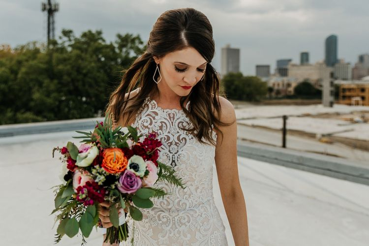 Bride in Sleeveless High-Neck Stella York Gown with Lace Overlay and Gold Underskirt | Half Up Half Down Wedding Hair | Bride Wearing Red Lipstick | Colourful Bridal Bouquet of Pink, Orange and White Flowers with Ferns, Eucalyptus and Greenery | Rifle Paper Co. Trainers for Informal Wedding in Fort Worth, Texas | Paul & Nanda Photography