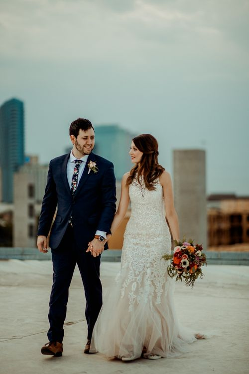 Bride in Sleeveless High-Neck Stella York Gown with Lace Overlay and Gold Underskirt | Half Up Half Down Wedding Hair | Bride Wearing Red Lipstick | Groom in Navy Suit and Floral Tie | Pink Buttonhole | Colourful Bridal Bouquet of Pink, Orange and White Flowers with Ferns, Eucalyptus and Greenery | Rifle Paper Co. Trainers for Informal Wedding in Fort Worth, Texas | Paul & Nanda Photography