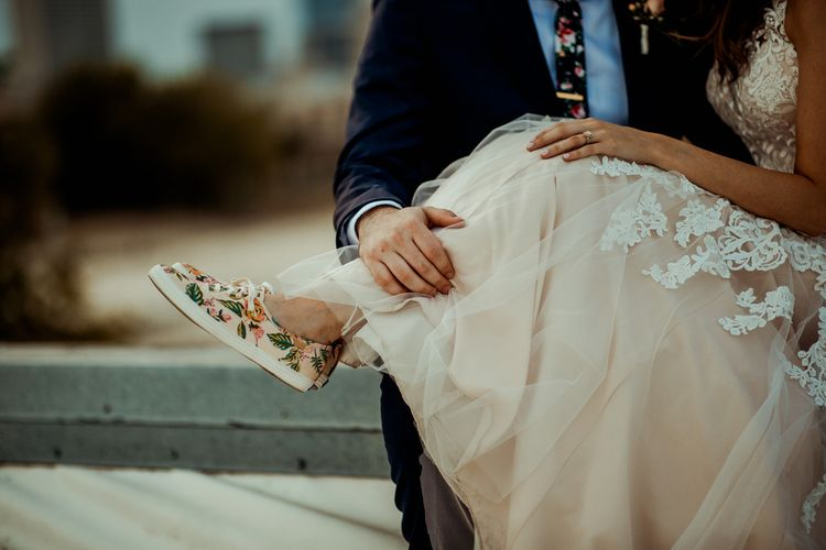 Blush Rifle Paper Co. Trainers with Pink Flowers and White Laces | Bride in Sleeveless High-Neck Stella York Gown with Lace Overlay and Gold Underskirt | Groom in Navy Suit and Floral Tie | Pink Buttonhole | Rifle Paper Co. Trainers for Informal Wedding in Fort Worth, Texas | Paul & Nanda Photography