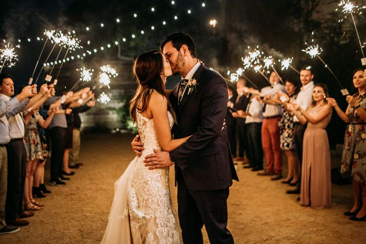 Sparkler Send Off | Bride in Sleeveless High-Neck Stella York Gown with Lace Overlay and Gold Underskirt | Groom in Navy Suit and Floral Tie | Pink Buttonhole | Festoon Lights | Rifle Paper Co. Trainers for Informal Wedding in Fort Worth, Texas | Paul & Nanda Photography