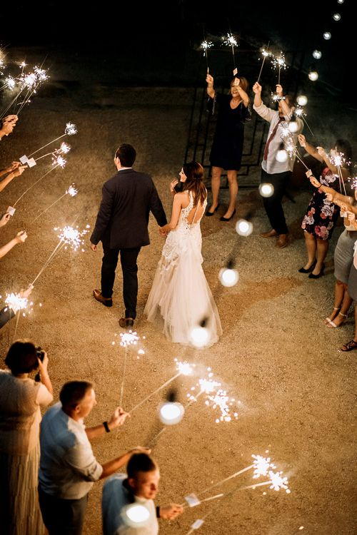Sparkler Send Off | Bride in Sleeveless High-Neck Stella York Gown with Lace Overlay and Gold Underskirt | Groom in Navy Suit and Floral Tie | Festoon Lights | Rifle Paper Co. Trainers for Informal Wedding in Fort Worth, Texas | Paul & Nanda Photography