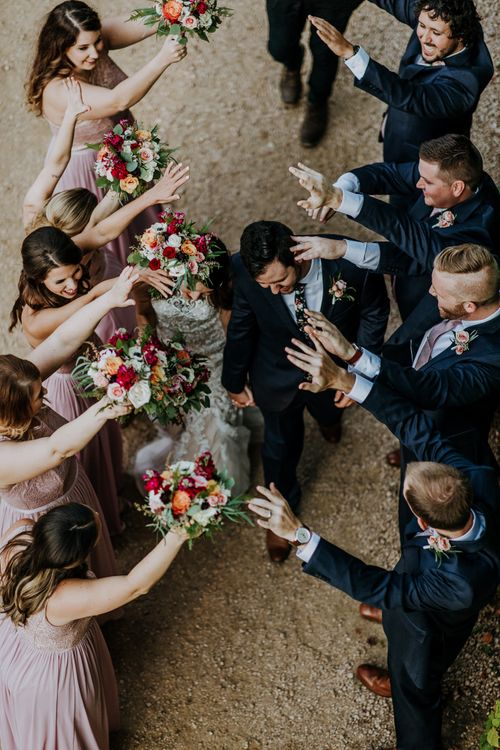 Bride in Sleeveless High-Neck Stella York Gown with Lace Overlay and Gold Underskirt | Groom in Navy Suit and Floral Tie | Bridesmaids in Pink Dresses with Lace Bodice | Colourful Bouquets of Pink, Orange and White Flowers with Ferns, Eucalyptus and Greenery | Groomsmen in Navy Suits and Silk Blush Ties | Pink Buttonholes | Rifle Paper Co. Trainers for Informal Wedding in Fort Worth, Texas | Paul & Nanda PhotographyRifle Paper Co. Trainers for Informal Wedding in Fort Worth, Texas | Paul & Nanda Photography