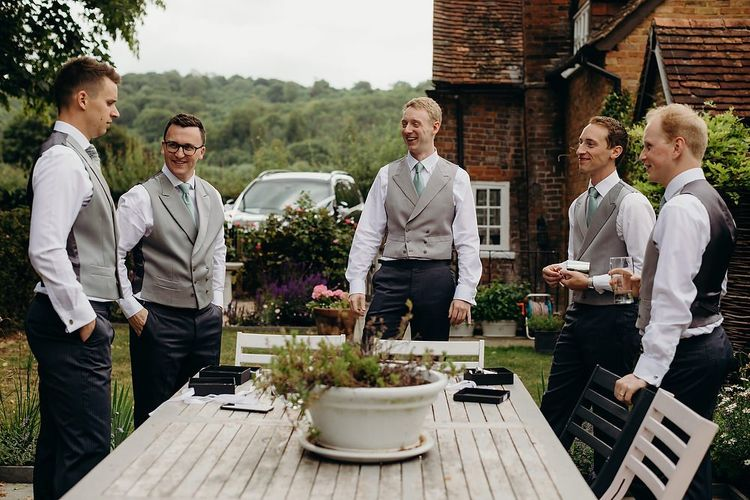 Groomsmen in matching grey waistcoats for pub wedding