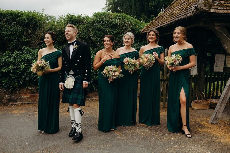 Bridesmaids in green dresses wait for bride in layered wedding dress