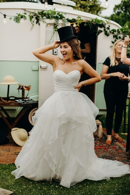 Bride poses with photo booth prop in layered wedding dress