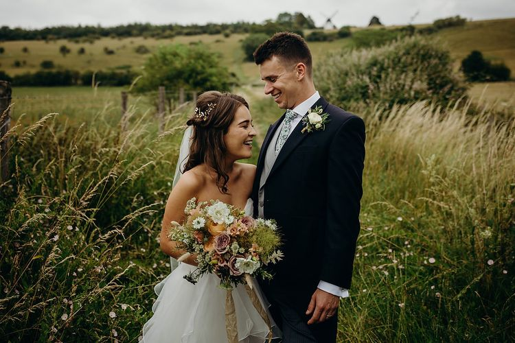 Bride in layered wedding dress with groom in morning suit