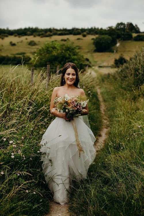 Bride clutching bouquet wearing layered wedding dress