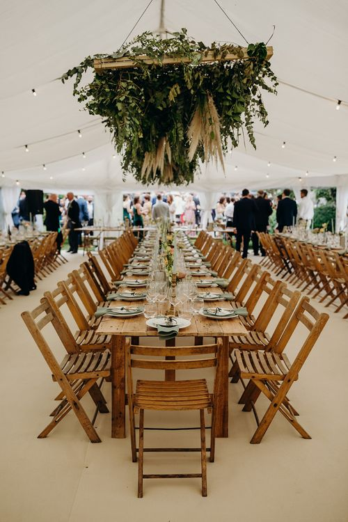 Long wooden banquet tables with foliage hanging installation