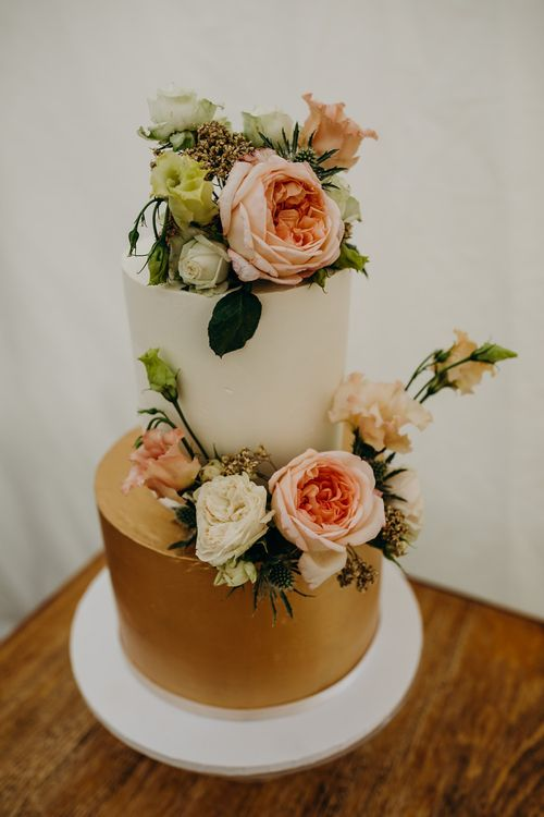 White and gold wedding cake with flower decor