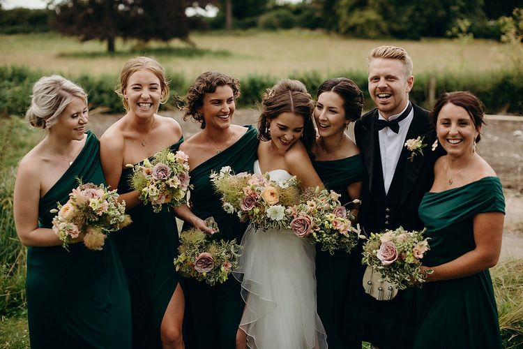Bride in layered wedding dress with bridesmaids in emerald green dresses