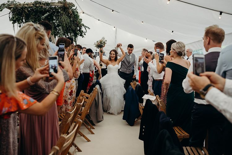 Bride in layered wedding dress enters marquee with new husband