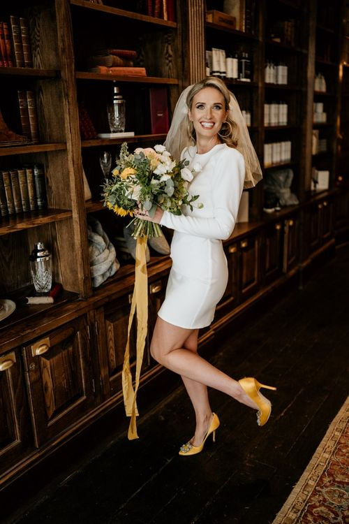 Stylish bride in short wedding dress with yellow bouquet and shoes