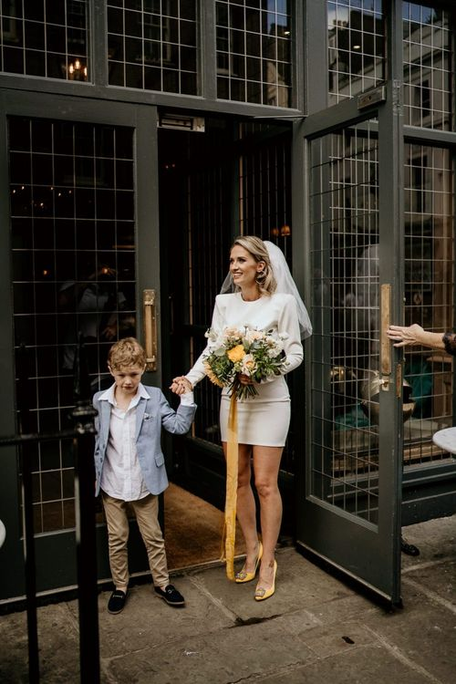 Bride in short wedding dress with yellow shoes holding her sons hand