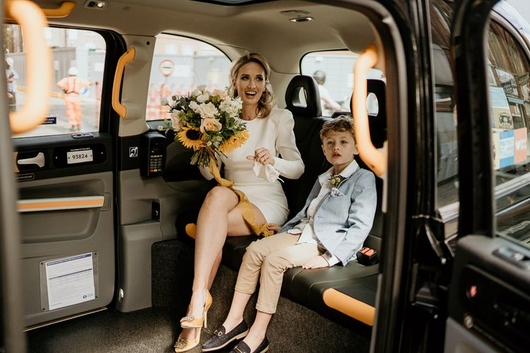 Stylish bride in short wedding dress and son in a taxi cab