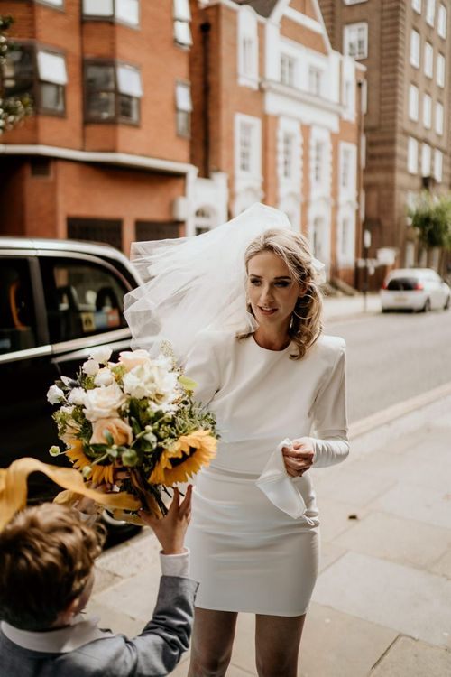 Stylish bride in Alex Perry short wedding dress and veil