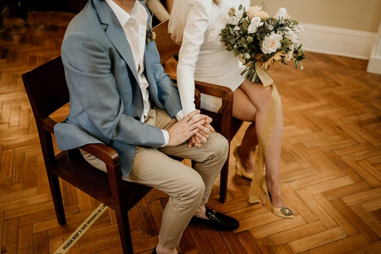 Bride and Groom holding hands during Town Hall wedding ceremony