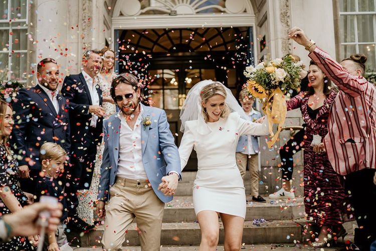 Confetti exit with bride in short wedding dress and groom in blue blazer and chinos
