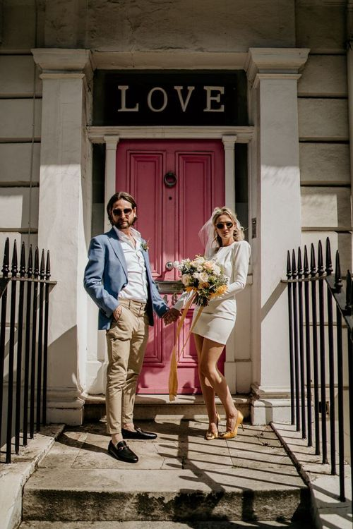 Stylish bride and groom standing on a doorstep with LOVE sign and pink door