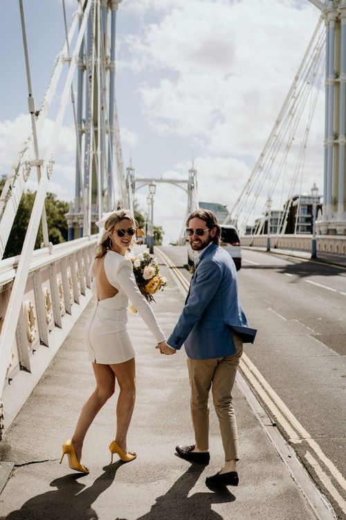Stylish bride and groom walking across at bride in London