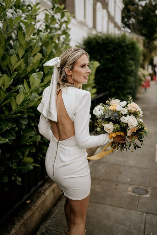 Stylish bride in Alex Perry wedding dress with low back and bow hair accessory