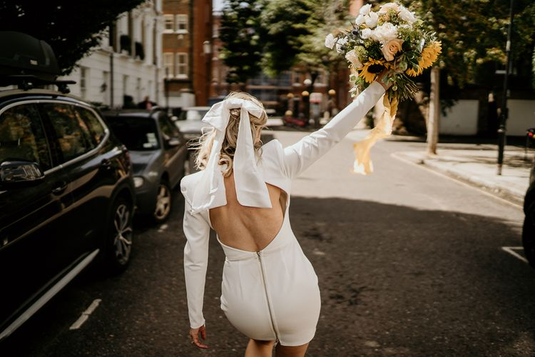 Bride in backless short wedding dress with bow hair accessory