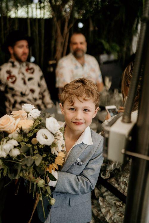 Little groomsman holding the yellow flower wedding bouquet
