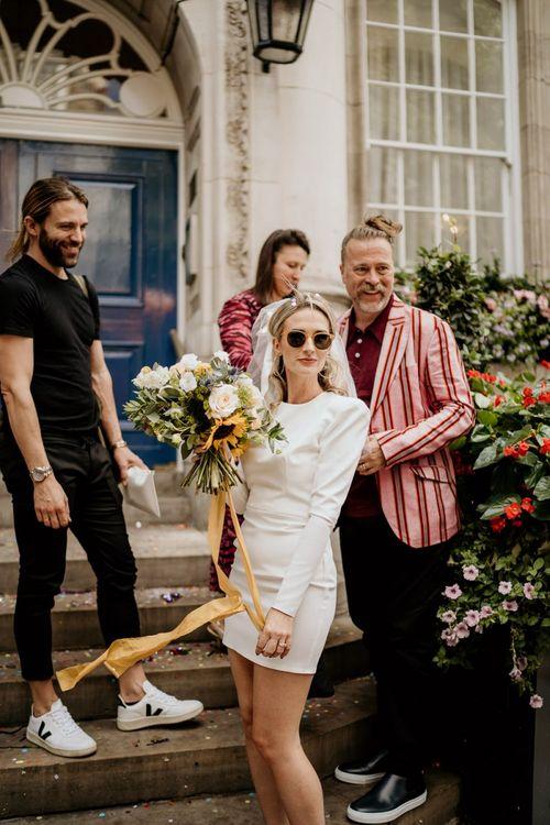 Stylish bride in short wedding dress and sunglasses