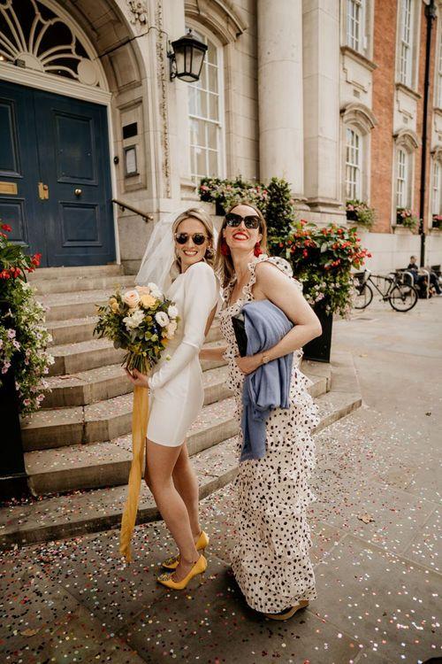 Stylish bride in short wedding dress with friend in polka dot dress