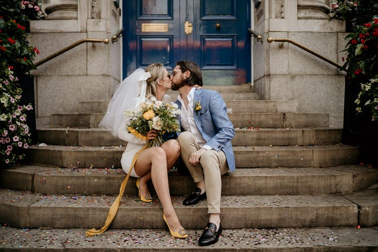 Stylish bride in short wedding dress with yellow shoes and bouquet and groom in blue blazer at COVID wedding
