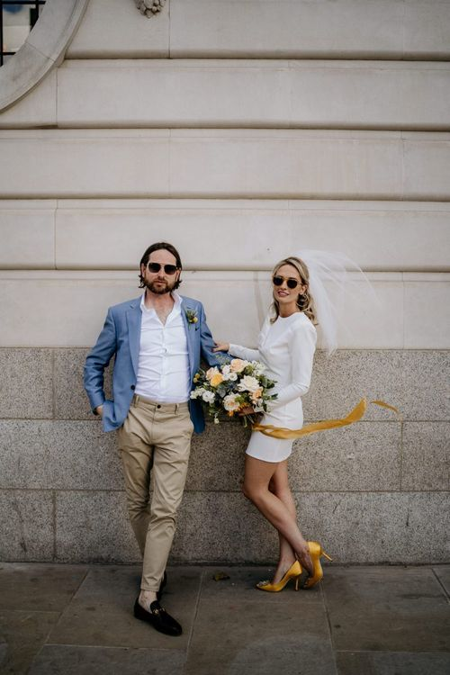 Stylish bride in short wedding dress and groom in blue blazer and chino at London wedding
