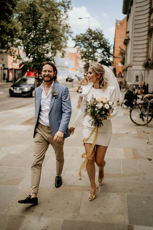 Stylish bride and groom walking through London