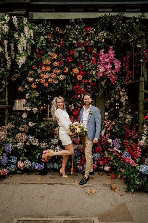 Stylish bride in short wedding dress and groom in blue blazer standing in front of a flower installation