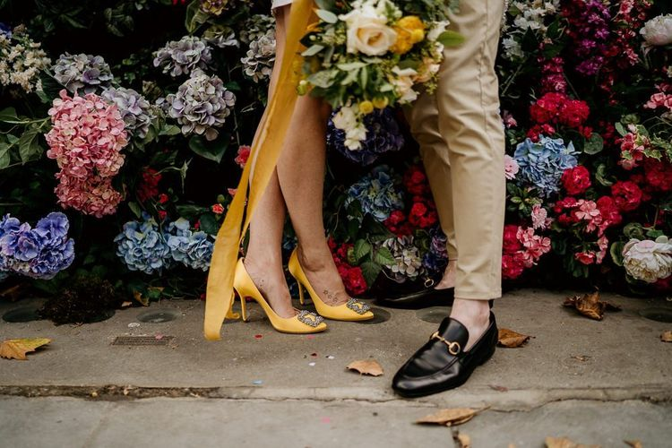 Bride in yellow Manolo Blahnik hangisi pump and groom in loafers