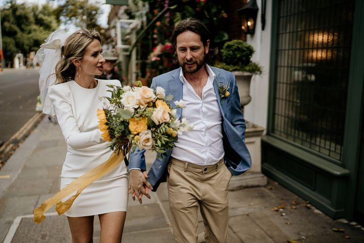 Bride and groom walking through London streets