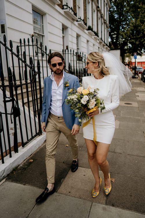 Portrait of bride and groom walking through London