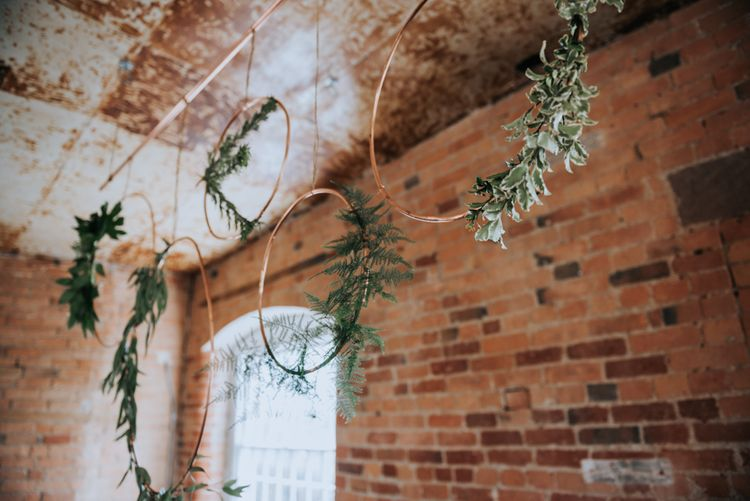 Copper Hoop Decor with Greenery | Pink Roll Top Booze Bath and Copper & Perspex Wedding Decor at Industrial Venue The West Mill | Rosie Kelly Photography