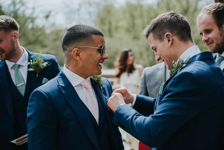 Groom in Navy Ted Baker Suit from Moss Bros. | Pink Roll Top Booze Bath and Copper & Perspex Wedding Decor at Industrial Venue The West Mill | Rosie Kelly Photography