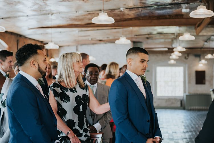 Wedding Ceremony | Groom at the Altar  in Navy Ted Baker Suit | Pink Roll Top Booze Bath and Copper & Perspex Wedding Decor at Industrial Venue The West Mill | Rosie Kelly Photography