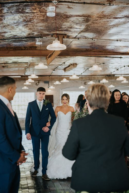 Wedding Ceremony Bridal Entrance  in Fishtail Allure Bridal Gown | Pink Roll Top Booze Bath and Copper & Perspex Wedding Decor at Industrial Venue The West Mill | Rosie Kelly Photography