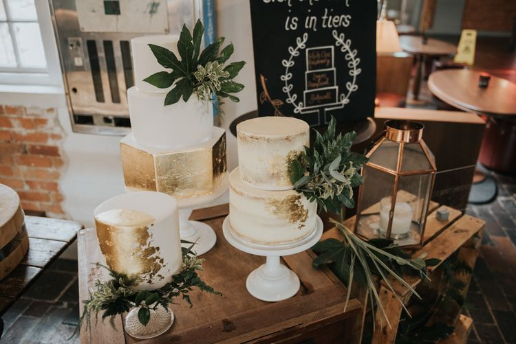 Gold Leaf & White Wedding Cakes with Hexagon Tier | Chalkboard Wedding Sign | Wooden Crates | Pink Roll Top Booze Bath and Copper & Perspex Wedding Decor at Industrial Venue The West Mill | Rosie Kelly Photography