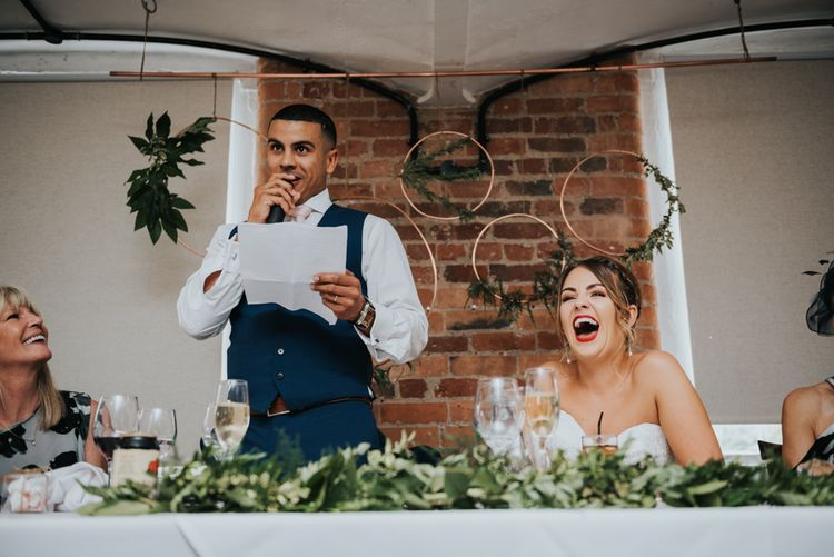 Wedding Reception Speeches | Hoop & Greenery Top Table Backdrop | Bride in Fishtail Allure Bridal Gown | Groom in Navy Ted Baker Suit | Pink Roll Top Booze Bath and Copper & Perspex Wedding Decor at Industrial Venue The West Mill | Rosie Kelly Photography