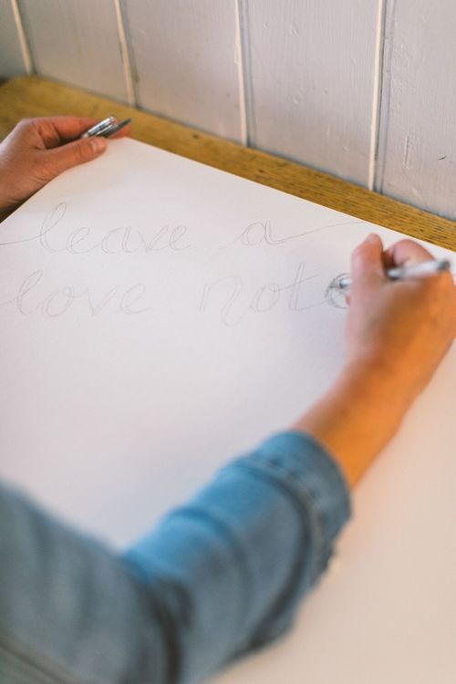 Person writing the words 'Leave a love note' onto a box canvas in silver pen
