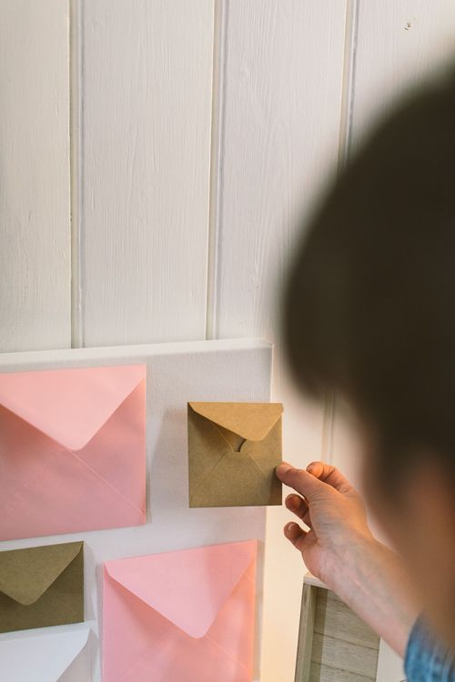 Person sticking a brown kraft envelope onto a white canvas as part of a DIY wedding card table