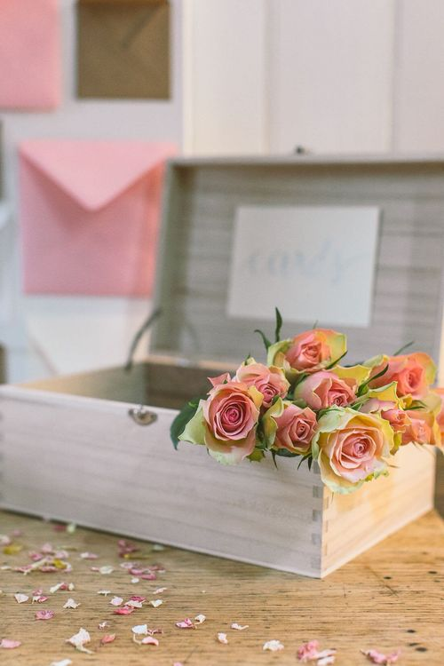 Bunch of pale pink antique roses inside a simple wooden card box