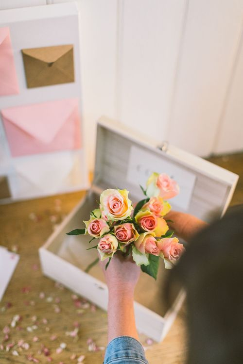 Person putting a bunch of pale pink antique roses into a card box as part of a wedding card table